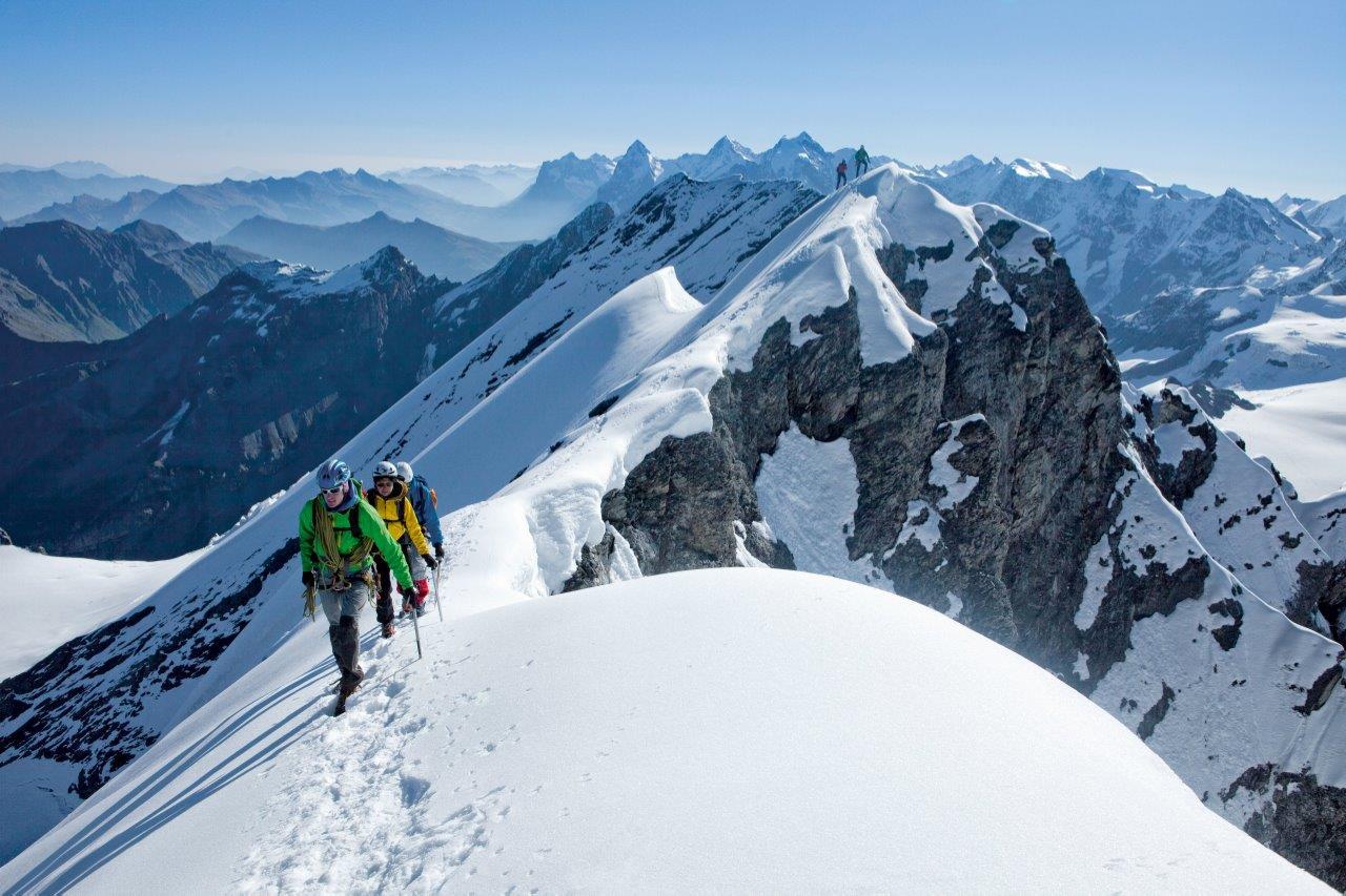 Tras los alpinistas que acceden a la cima del  Bluemlisalphorn se ven el Eiger, Moench y Jungfrau. (Copyright/ST/Swiss Image).